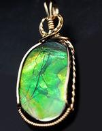 新緑を思わせるグリーンを中心に朱色が混ざる美しいアンモライト(Ammolite)を使ったペンダントトップ。金具は14金ゴールドフィルを使用。チェーン、革紐、高級ジュエリーケース付き。